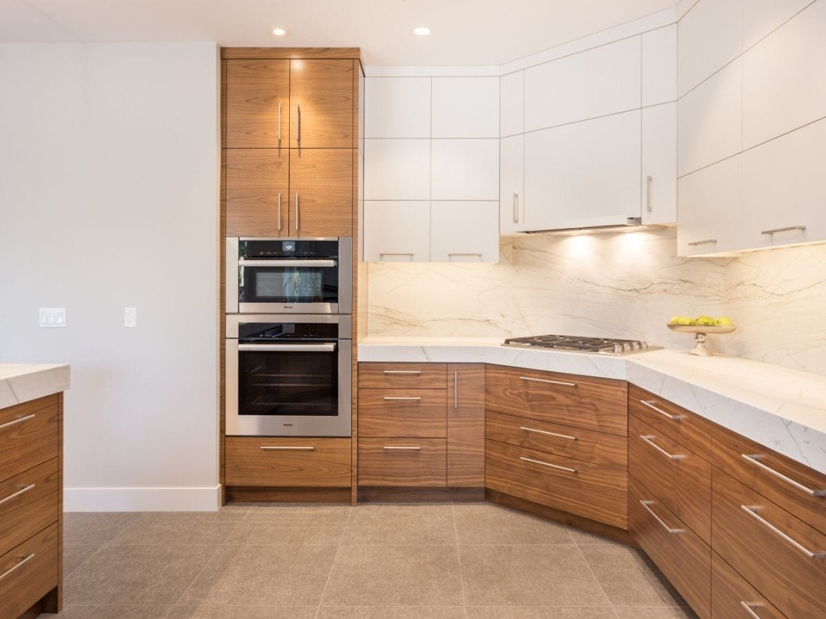 Remodeled kitchen with white upper cabinets and light wood lower cabinet